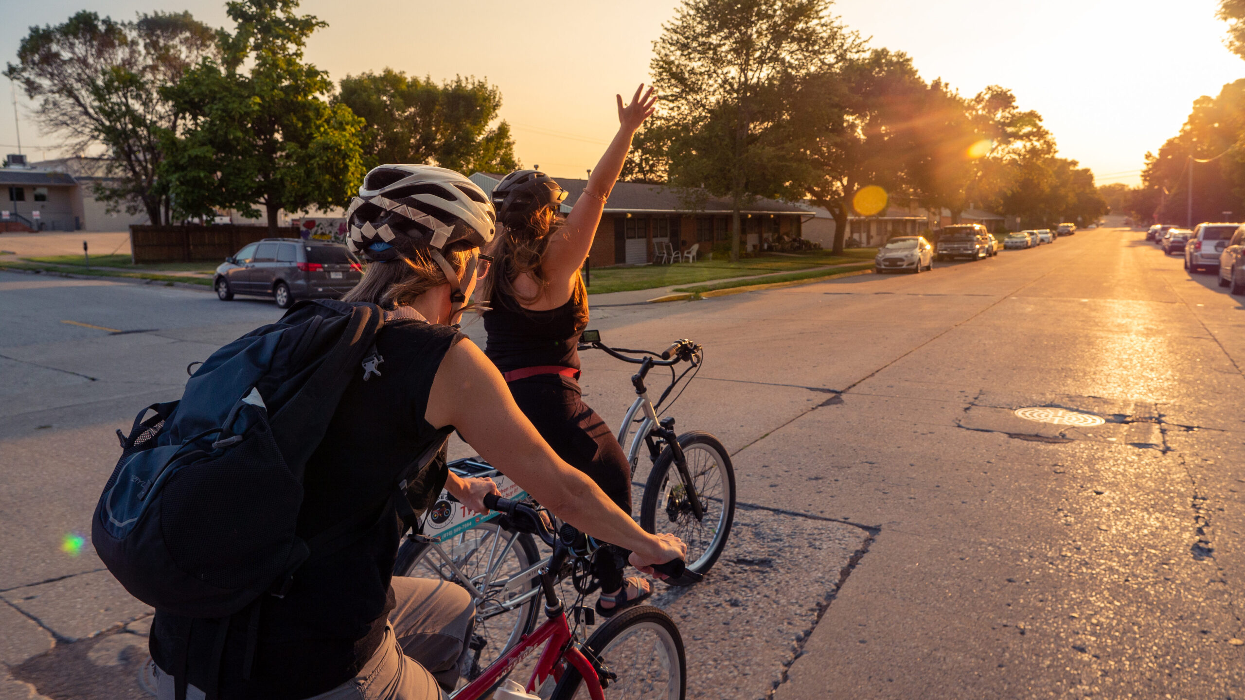 Woman riding bike with hand up into sunset