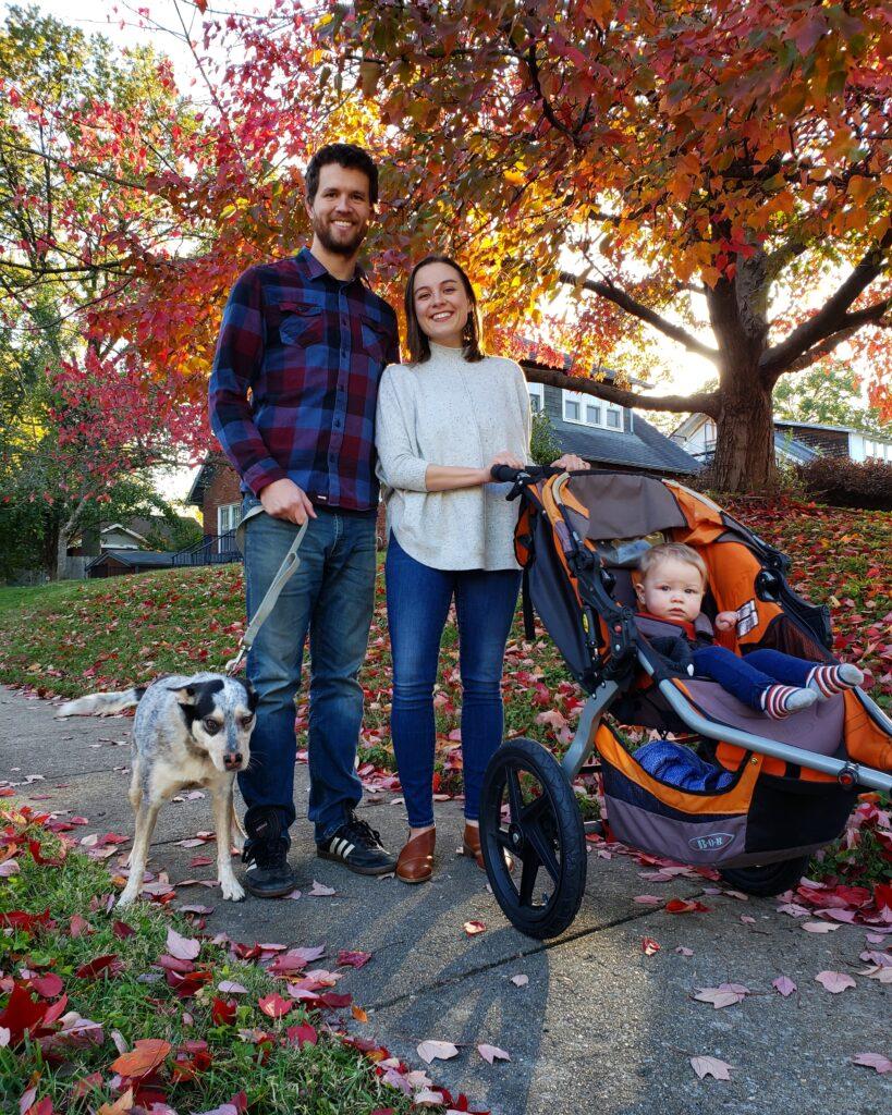 Man, woman, baby in stroller, dog on bike boulevard