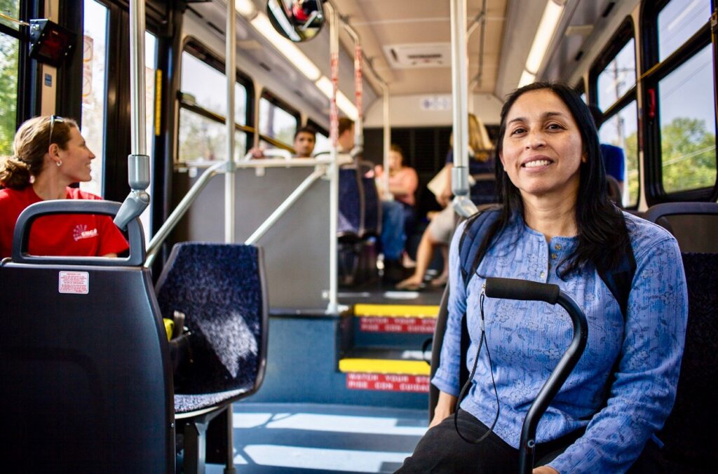 Woman sitting on bus with cane